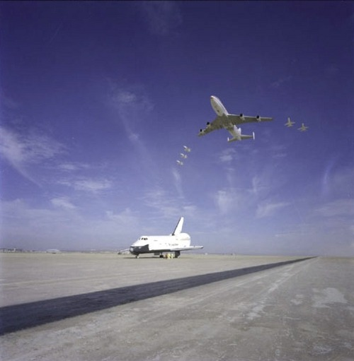 """This impressive scene was photographed when the NASA 747 carrier aircraft and five T-38 aircraft flew over the Space Shuttle Orbiter 101 ""Enterprise"" while it was parked on the runway at Edwards Air Force Base in Southern California. The Orbiter 101 had just completed a five-minute, 31-second unpowered mission during the second free-flight of the Space Shuttle Approach and Landing Test series, on September 13, 1977, at the Dryden Flight Research Center.""(via)"