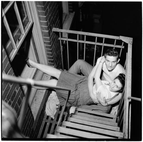 mills:  Park Benches - Love is Everywhere [Couple flirting on a fire escape], 1946, by Stanley Kubrick. More can be seen at the Museum of the City of New York. He took an astonishing number of perfect photographs.  I'd like this, I'd probably be scared to death being on a fire escape but this would be nice regardless