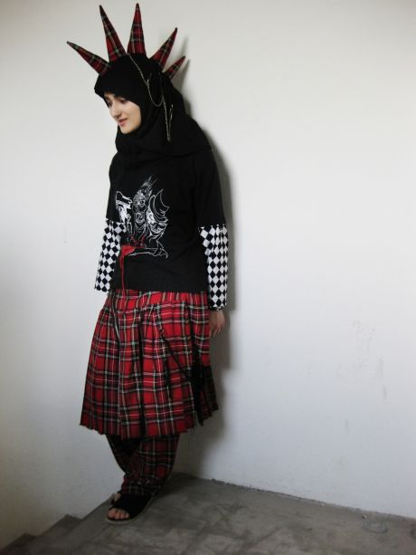 "taqwaacore:  Tesnim Sayar is a Muslim punk. She wears both the headscarf and a mohawk and dreams of living of her own design. And like other supporters of the Muslim punk movement Taqwacore, she sees no contradiction between punk and Islam ""I'm tired of people's generalizations and stereotypes about Muslim girls. Therefore, I am punk, 'says 21-year design student Tesnim Sayar, who calls herself a Muslim goth-punk."" Photo: Kristina Ask  Since Tesnim Sayar was 12 years old, she bought her first rivet bracelet. She paid an '50s for it in a different alluring shop in Odense.Since then ""pighalsbånd"", ring in the nose, piercing the lower lip and safety pins in clothes crept into her wardrobe. And then a mohawk of black plastic that can be zipped on and off her headscarf.Tesnim Sayar was born in Denmark but have Turkish roots and have worn a headscarf since she was eight years. Today she is 21 years and calls herself a Muslim goth-punk. She designs clothes in Kolding Design School, where she goes to a fashion design line. ""When I was younger, I thought it was hard to find clothing that was both smart and enveloping. The smart was too low cut, and so it was soon to layer upon layer, where I came to look like an old grandmother. I would change that, ""says Tesnim and gesturing enthusiastically with his fingerless gloves with imprint of skeleton hands while the chainbracelet rattles. Tesnim is not the only one that unites two worlds that seem difficult compatible. The Muslim punk movement Taqwacore today has followers all over the world. In prayer on pizza boxesActually, the movement began as pure fiction, as the 32-year-old author Michael Muhammad Knight 2003 published the novel in 2003 called The Taqwacores about a Muslim punk collective in Buffalo. Among the residents are Muslim gays, a burqa clad punk girl who shares blowjobs out Sufis with mohawks, Indonesian skaters and high Muslim skinheads who use pizza boxes as prayer rugs. Their living room, where there is a hole in the wall in the direction of Mecca, contains both celebrations and prayer which are advertised to the sound of electric guitar. The residents' lives consist of sex, dope, and religion, while cultivating an Islamic punk subculture called Taqwacore derived from the words hardcore and the Arabic word to be God conscious, Taqwa. Since Tesnim Sayar bought her first rivet bracelet the book about the taqwacore was not yet written, but Tesnim already knew that she wanted to design clothes, and that she was attracted to things that were different. So it still is. ""I go with it, because I think it's cool and fits me. I have not designed it to provoke. But my message is also that one should refrain from thinking that Muslim girls are sitting at home and are boring,"" says Tesnim in the Youth House on Dortheavej in Copenhagen.""One of my friends says that one defines a punk as someone who is opposed to some form of oppression. I'm tired of people's generalizations and stereotypes about Muslim girls. Therefore, I am punk,"" says Tesnim.Out of respect for her parents she takes off her mohawk & keeps the scarf and is content to keep the rivets on when she visits her family in Odense. Their vision of Islam is otherwise very similar to her own, she emphasizes. It is knowledge rather than tradition.""I do not think Islam is oppressive, but I am against blindly to live by traditions, whose background is unknown. The more you know, the more free you become. That's what my parents taught me,"" says Tesnim who can not see why punk should clash with Islam. Muhammad as punkAbout the same time that Tesnim Sayar puts the first safety pin stuck in the headscarf and expands the collection of rivet bracelet, begins the novel about the Taqwacores to gain a cult status among young Muslims who have difficulty finding their place between the patriarchal family patterns, rules from the home country and a society who will not recognize them.In Texas, sits one of the young people who find it difficult to let the book go again. The 15-year-old Iranian American, Kourosh Poursalchi, contacts Michael Muhammad Knight so he could be associated with a band from the book. He thinks, that the book's universe is real. When he was disappointed to find out that the Muslim punk collective was just fiction, he creates his own version of Taqwacore by adding music to an excerpt of the book. It will be for the song ""Muhammad was a punk rocker.""A new music genre called taqwacore born, and with the novel and the new music genre follows a subculture and an ideological meeting point for young Muslim punks. A movement that offers both Western prejudices and radical Islamists the middle finger. Most of Tesnims friends think that her clothing style is bold. But even though she hates it when other people to decide how she should look, she would never take her clothes on when she is visiting Turkey.""There's just someone who is going to drive into somethig if I come walking in the street in this outfit. Or I'm going to the hospital of people with a mental illness."" She laughs and tells of the many responses she gets on the streets in Copenhagen.An old man had difficulty moving his walker quickly enough that he could follow her with his eyes. Another car stopped and yelled at her.""And a woman stopped on the street and said, no, no, no, after which I replied yes, yes, yes, says Tesnim and demonstrates how the mohawk can be zipped off.She dreams of a living of designing clothes. Whether it is clothing for Muslim punks, she does not know yet. At least she doesn't expect dropping the rivets and mohawk right away.""Maybe I'll put the mohawk away when I turn 60 I do not know. Who knows, maybe I'll have to walk around with a skull on my stick."" (Source. Translated from danish to english by me)   This is really interesting."