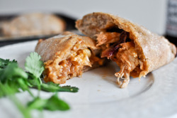 Mini Whole Wheat BBQ Chicken Calzones Dough Ingredients: 1 1/8 cups warm water (100-105 F degrees) 3 teaspoons active dry yeast 1 1/2 tablespoons honey 1 1/2 tablespoon olive oil 2 cups 100% whole wheat flour 1 cup all-purpose flour 1 teaspoon salt  Filling Ingredients: 1 red onion, thinly sliced 1/2 tablespoon olive oil 1 1/2 boneless, skinless chicken breasts, cooked and shredded 1/4 teaspoon onion powder 1/4 teaspoon smoked paprika 1 cup of your favorite bbq sauce + more for dipping 4 ounces freshly grated cheddar cheese 4 ounces freshly grated provolone cheese fresh cilantro, if desired  Dough Directions: In a large bowl, combine water, yeast, honey and olive oil. Mix with a spoon, then let sit until foamy, about 10 minutes.  Add in the whole wheat flour and salt, mixing until the dough begins to come together. Since it will probably still be sticky, add in another 1/2 cup of all purpose flour, kneading the dough with your hands and then turning it onto a work surface to knead for a few minutes. If dough is still sticky, add the remaining flour until it is soft, smooth and stretchy. Rub the same bowl with olive oil then place the dough inside, turning to coat. Cover with a towel and place in a warm place to rise for about 1 1/2 hours. Once risen, punch down the dough and knead a few times, adding a few spoonfuls of flour if sticky. Separate the dough into 6 or 8 pieces (it's your call), then roll into a ball and place covered on a baking sheet to rise for another 10 minutes.  Filling Directions: While dough is rising, heat a skillet over medium-low heat and add olive oil. Toss in onions with a sprinkle of salt, then cover and let caramelize for 15-20 minutes, stirring occasionally. Preheat oven to 375 degrees. In a bowl, combine chicken with garlic powder and smoked paprika. Assembly: Roll each ball of dough into a small oval, then fill with a few spoonfuls of bbq sauce, shredded chicken, a handful of caramelized onions and a sprinkle of both cheeses. Toss in cilantro if desired. Drizzle a bit of additional sauce on top, then fold the top over to meet the bottom, tightly sealing the edges. Poke a few holes in the top with a knife or fork. Place calzones on a non-stick baking sheet and bake for 20-25 minutes, or until golden brown.