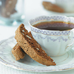 Coffee-Hazelnut Biscotti Ingredients: 2 tablespoons Frangelico (hazelnut-flavored liqueur) 2 tablespoons unsweetened cocoa 1 teaspoon instant espresso or 2 teaspoons instant coffee granules 1 teaspoon vegetable oil 2 large egg whites 1 large egg 1 1/3 cups all-purpose flour 1/2 cup whole-wheat flour 1/2 cup granulated sugar 1/2 cup packed brown sugar 1/2 cup coarsely chopped toasted hazelnuts, divided 1 teaspoon baking soda 1/8 teaspoon salt 2 teaspoons ground coffee beans Cooking spray Directions: Preheat oven to 300°. Place liqueur in a small bowl. Microwave at HIGH 10 seconds. Stir in cocoa and espresso until smooth.  Add oil, egg whites, and egg, stirring with a whisk until blended. Lightly spoon flours into dry measuring cups, level with a knife. Place flours, sugars, 2 tablespoons hazelnuts, baking soda, and salt in a food processor; process until hazelnuts are ground.  Add ground coffee; pulse 2 times or until blended.  With processor on, slowly add liqueur mixture through food chute; process until dough forms a ball.  Add 6 tablespoons hazelnuts; pulse 5 times or until blended (dough will be sticky).  Turn dough out onto a floured surface; knead lightly 4 to 5 times. Divide dough into 3 equal portions, shaping each portion into a 10-inch-long roll. Place rolls 3 inches apart on a large baking sheet coated with cooking spray. Bake at 300° for 28 minutes. Remove rolls from baking sheet; cool 10 minutes on a wire rack. Cut each roll diagonally into 20 (1/2-inch) slices. Place slices, cut sides down, on baking sheets. Bake at 300° for 20 minutes. Turn cookies over; bake an additional 10 minutes (cookies will be slightly soft in center but will harden as they cool). Remove from baking sheets; cool completely on wire racks.
