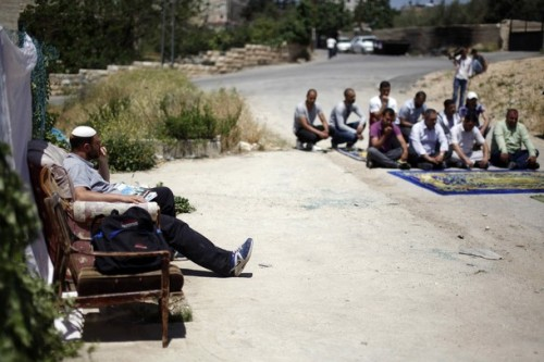 "An extremist Jewish settler watches a Palestinian family — whose home he is now occupying — perform Friday prayers outside their former residence in Israeli annexed East Jerusalem's Beit Hanina neighborhood, on April 27, 2012, after they were evicted last week, as Israel continues its ethnic cleansing of Palestinians in its goal to ""Judaize"" East Jerusalem. (Photo: Getty Images)"