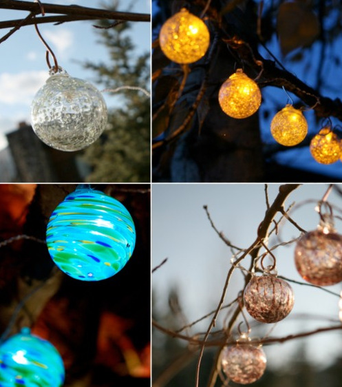 """Illuminate your outdoor spaces with beautiful and festive solar powered hand-blown glass string lights. Six lights crafted from colored and clear hand-blown glass and luminescent details adorn a clear wire and come complete with six high powered LED lights and copper hanging hooks. Aurora Glow string lights are powered by the sun, with a solar panel located nearly 15 feet away from the first glass globe."""