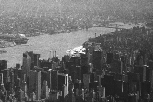 seanaes (via bopuc)  Piggyback Space Shuttle Enterprise over NYC.  In 1983.  That's probably the year the shuttle prototype came to Stansted. I remember it happening, and regret that, for some reason, when my dad got out of the car to take a photograph of it, I didn't go with him. Still, I expect I'll finally get to see it Enterprise at USS Intrepid some time later this year. (Photograph: Richard Drew / AP)