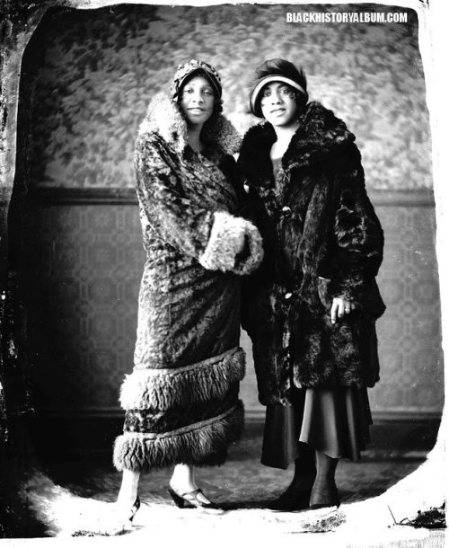Two unidentified, fur-bedecked African American women dressed in classic flapper style smile for the camera, circa 1920s. Addison Scurlock, photographer. African American vernacular photography via Black History Album via Flickr. 2 of 2 FOLLOW US VIA TWITTER | FACEBOOK | FLICKR | RSS | PINTEREST