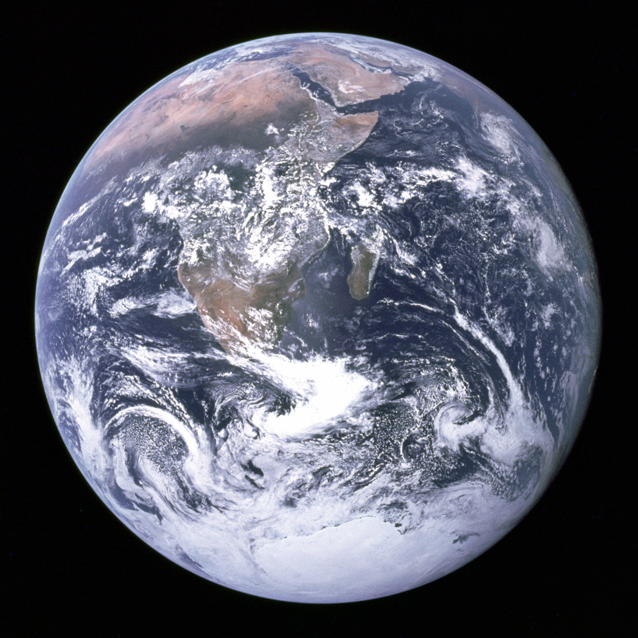 "The original Blue Marble photograph, with caption…""View of the Earth as seen by the Apollo 17 crew traveling toward the moon. This translunar coast photograph extends from the Mediterranean Sea area to the Antarctica south polar ice cap. This is the first time the Apollo trajectory made it possible to photograph the south polar ice cap. Note the heavy cloud cover in the Southern Hemisphere. Almost the entire coastline of Africa is clearly visible. The Arabian Peninsula can be seen at the northeastern edge of Africa. The large island off the coast of Africa is Madagascar. The Asian mainland is on the horizon toward the northeast."" Apollo 11"