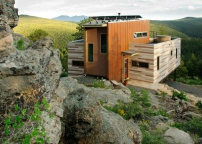 More cargotecture — Colorado house constructed from shipping containers  This project questions the need for excessive space and challenges occupants to be efficient. Two [retired] shipping containers saddlebag a taller common space that connects local rock outcroppings to the expansive mountain ridge views. The containers house sleeping and work functions while the center space provides entry, dining, living and a loft above. The project is planned to be off-the-grid using solar orientation, passive cooling, green roofs, pellet stove heating and photovoltaics to create electricity.  Designed by Studio H:T, whose principals were involved in the design of this University of Colorado student project built from pallets and various found materials.