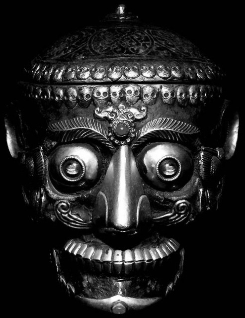 "midnight-gallery:   kapāla, (Sanskrit: ""skull""), Tibetan thod pa, cup made of a human skull, frequently offered by worshipers to the fierce Tantric deities of Hindu India and Buddhist Tibet. In Tibet the skull cup is displayed on the Buddhist altar and is used in ritual to offer to the ferocious dharmapāla (""defender of the faith"") divinities either wine, which symbolizes blood, or dough cakes, which are shaped to resemble human eyes, ears, and tongues. The skull cup is often a handsomely worked object and rests on a triangular pedestal representing a sacrificial fire with skulls. The cup is mounted in metal, usually heavily embossed silver or gilt bronze, and topped with a lid shaped like half a skull, with a vajra- (""thunderbolt-"") shaped handle.  Source: http://www.britannica.com/EBchecked/topic/311715/kapala"