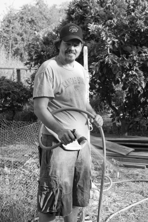 Young Man Watering His Veggie Garden in Black & White. UC Davis, 04-23-12. This was is really cool. I wandered into the veggie garden plots off the main campus, right off student housing, and this guy was there, working on his plot of land. He was super cool, a Mid-West US born and raised grad student who doing his grad work in Denmark. (Sweden?) He and his wife came back to the US so he could go to work at Davis. He was so cool that I felt comfortable enough to ask him if I could take his picture. He said yes, and I snapped three. They all pretty much looked the same, so I picked this one. I was so happy that I got over my fear of talking to strangers and asking strangers if I could take their picture. Well, this was a start.  Re the gardens, he told me it costs, annually, about $35 for a 200'x200' plot; there are many sizes and prices. Any faculty, student or staff can rent them. Water included.  I am tempted. For real.
