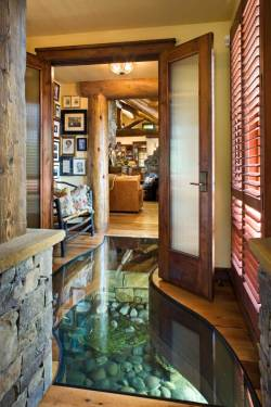 origami-dolls:  The foyer in a house built over a creek, in Wyoming. Built from reclaimed wood, a concept developed by artist Debbie Petersen and her late husband. The home's geo-thermal cooling system uses a pump to channel ground water through conduits under the house, which doesn't just save energy - it also creates the innovative glass-covered indoor stream.
