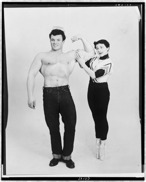 locpix:  Mr. America flexes his muscles as ballerina Marie Jeanne holds his left bicep. 1954