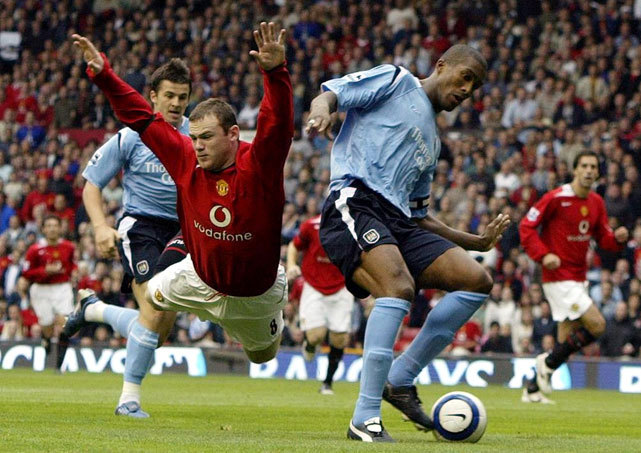 Wayne Rooney is tripped up by Sylvain Distin during a 2005 match between Manchester United and Manchester City. The game ended in a 1-1 draw. The two rivals face off today in a match that could decide the Premier League title. (AP/Phil Noble) MACINTOSH: Can City end United's reign of supremacy in Manchester?