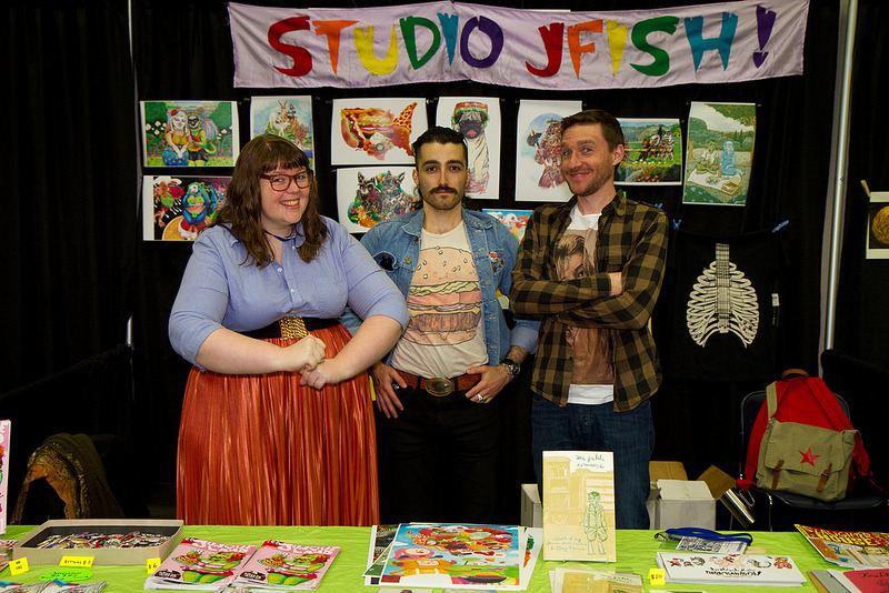 snakebomb:  STUDIO JFISH AT STUMPTOWN COMICS FEST 2012: robin bogert, jason fischer, greg khmara! <3  This is an honest depiction of our presence at Stumptown Comics Fest. I am smiling inside that moustache.