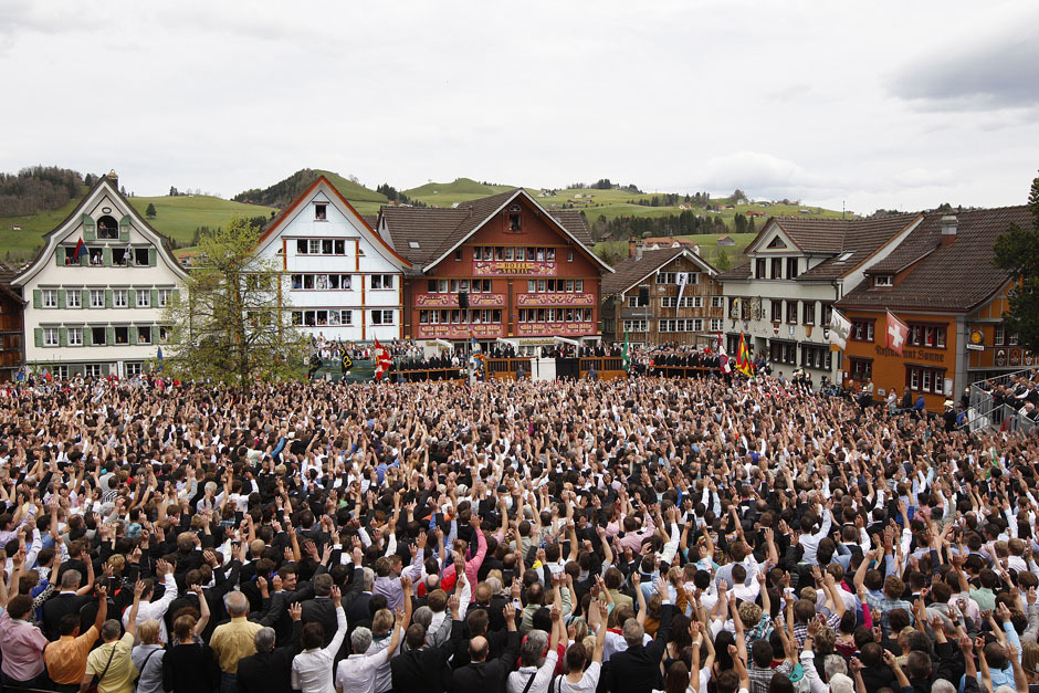People raise their hands to vote during the annual Landsgemeinde meeting at a square in the town of Appenzell, April 29, 2012. Appenzell is one of Switzerland's two remaining Landsgemeinden, a 700-year tradition of an open-air assembly in which citizens can take key political decisions directly by raising their hands. [Credit : Christian Hartmann/Reuters]