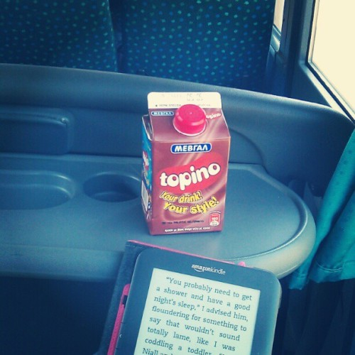 Reading on the bus and drinking.