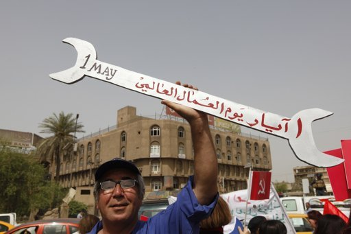 An Iraqi worker holds a spanner-shaped placard during a May Day rally in Baghdad May 1, 2012.