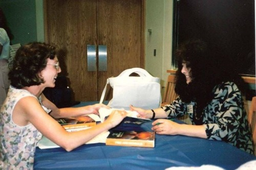 "Horn Book editor Martha Vaughan Parravano gets her books signed by Diana at Children's Literature New England 1988. The theme that year was ""The Heroic Ideal,"" and the speech Diana gave is in the back of the Firebird edition of Fire and Hemlock. (Note the two hardcovers in the photo!) Thanks to KT Horning, who took the picture."