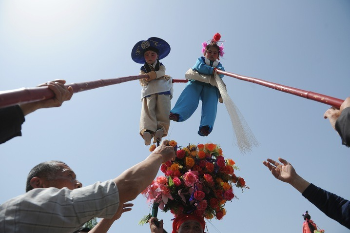 "newshour:  Villagers in Zhengyangguan, in China's eastern Anhui province, raise two children dressed as a deities onto poles. The ""floating ballet"" is an annual ritual once celebrated in many other villages but is now on the decline with fewer children now participating. (Photo by AFP/Getty Images)  ~reblogged by Trent Gilliss, senior editor"