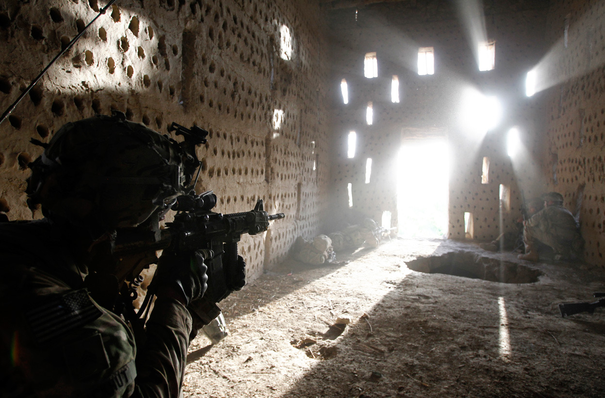 From Afghanistan: April 2012, one of 41 photos. U.S. soldier Nicholas Dickhut from 5-20 infantry Regiment attached to 82nd Airborne points his rifle at a doorway after coming under fire by the Taliban while on patrol in Zharay district in Kandahar province, southern Afghanistan, on April 26, 2012. (Reuters/Baz Ratner)