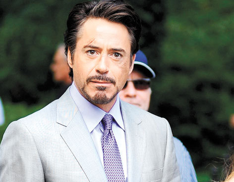 [Image: A production still of Robert Downey Junior during the Avengers.  He's wearing a light coloured suit and a patterned purple tie, and has a cut on his forehead above his right eyebrow.]