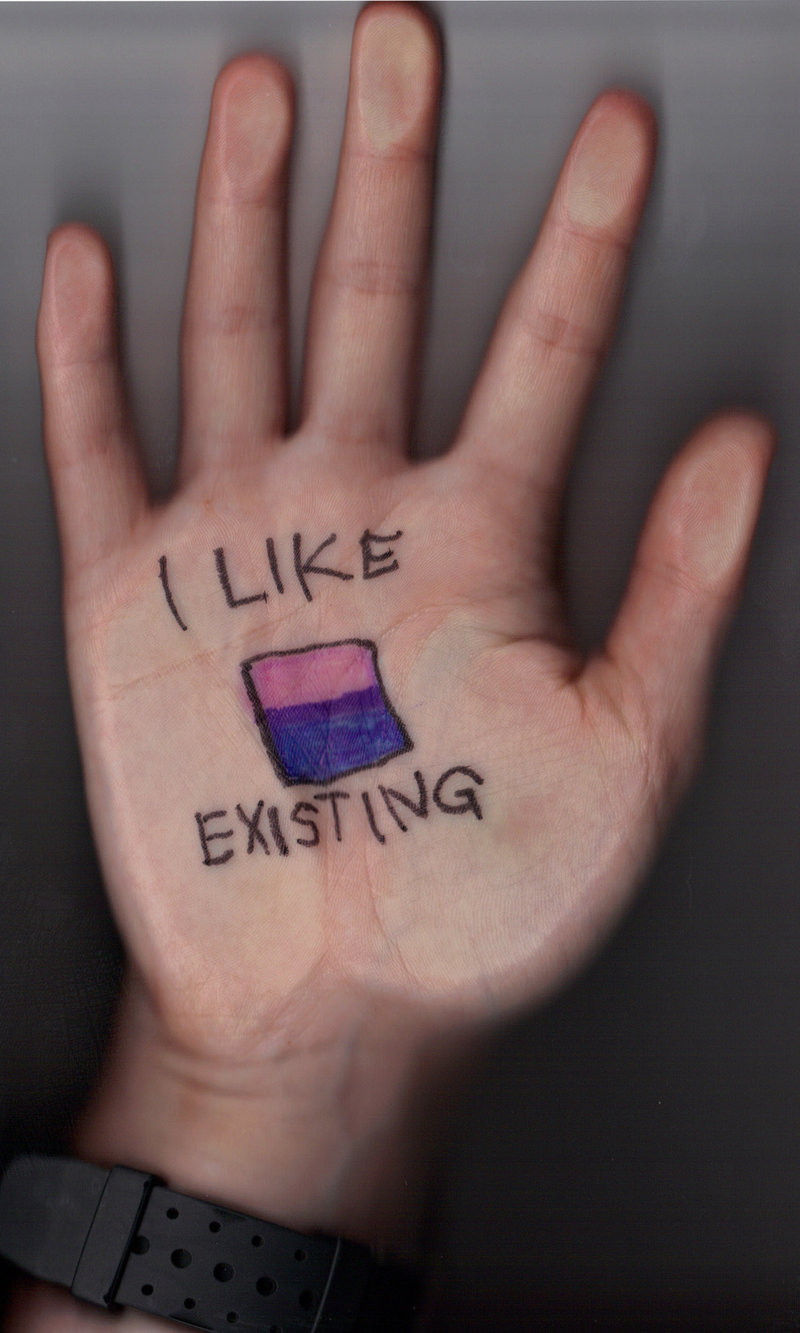 "A photo of someone's palm with a hand drawn square-ish bisexual pride flag (three horizontal stripes: top Rose = representing possibility of Same Gender attraction; bottom Blue = representing possibility of Different Gender attraction; and where the stripes overlap in Lavender = representing possibility of attraction Anywhere along the Entire Gender Spectrum).  Above the flag is written ""I Like"" and below the flag the statement finishes with the word ""Existing""."