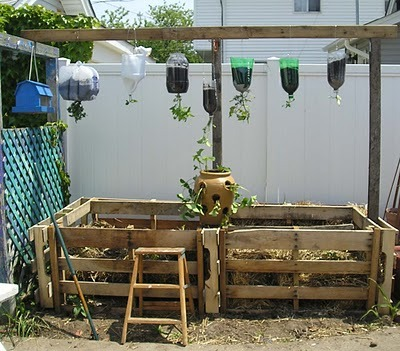 Today's pallet fix: Pallets repurposed to contain a compost pile. Also: Plastic bottles used as planters. Lots of reuse pictured here! (photo via The Reuser: A study in reuse archive)