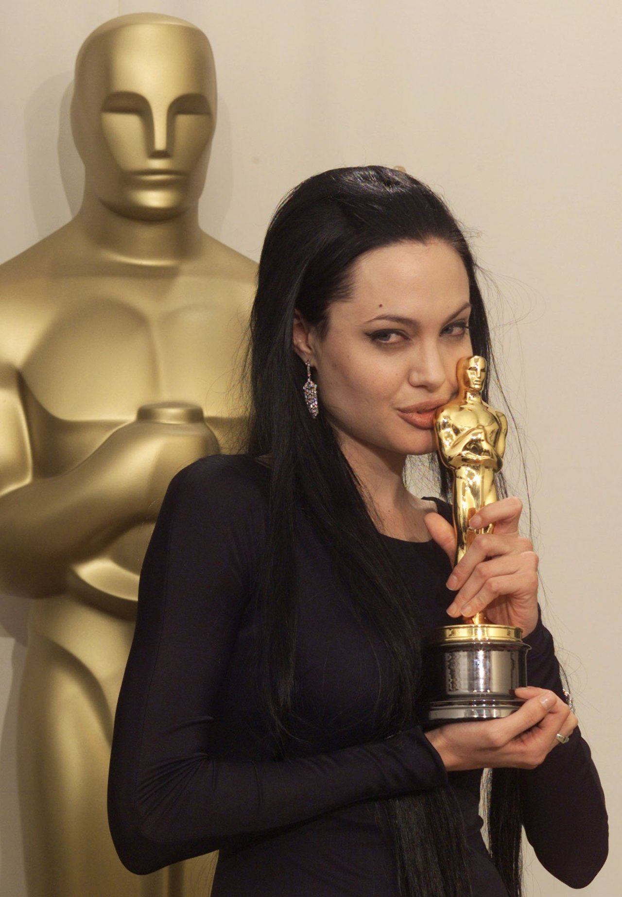 Angelina Jolie kissing her oscar for best supporting actress for her role in Girl, Interrupted at the 2000 Academy Awards