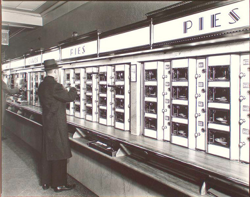 nypl:  You'll be able to see an actual Automat machine at our new exhibition, Lunch Hour NYC, opening June 22!! apossiopeza:  Automat, 977 Eighth Avenue, Manhattan. by New York Public Library on Flickr. Man takes pie out of Automat, stone counters and walls below metal and glass display.   It saddens me to live in a world without pie machines.