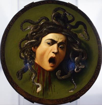 Caravaggio, Medusa, 1595-8 (Florence, Italy, Uffizi Gallery)  In 1598, Cardinal Francesco Maria del Monte gave this artwork to the Grand Duke Ferdinando I. The Medusa is painted on canvas applied to a wooden shield. The subject is mythological, referring to Athena's shield which was cunningly used to exploit the Medusa's power to petrify people. The Medici often made use of this iconography to represent their military power. Rather than basing the painting on ancient sources, Caravaggio captures the expression on the Medusa's face, deformed as it is in horror at having been beheaded, while even the mane of serpents writhes in all directions. — based on Google Art Project