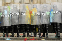 fotojournalismus:  Riot policemen stand guard after getting splattered by paintballs from student protesters during clashes on International Workers' Day, or May Day, at the central square of Bogota May 1, 2012. [Credit : Jose Miguel Gomez/Reuters)