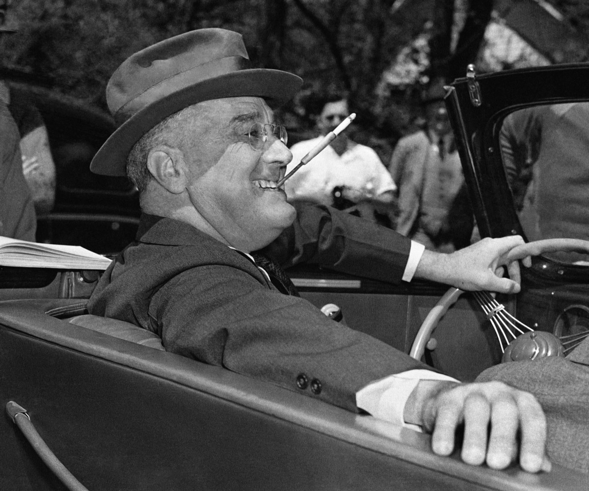 Warm Springs, Ga. April 1939. Cigarette holder at a jaunty angle, President Franklin Delano Roosevelt sits at the wheel of his car, fielding questions at an outdoor news conference. (AP)     An exhibit of Associated Press images of American Presidents opens today at Federal Hall in Manhattan. It will be on view through 2012. More information is available here.