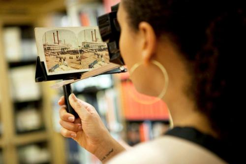 "Jesmyn Ward, author of Salvage the Bones, looking at a stereoscopic photo from the NYPL's photos & prints collection. Notice her wrist, which reads: ""love brother"". See more photos by LIVE's photographer Jori Klein from last night on our Facebook page…"