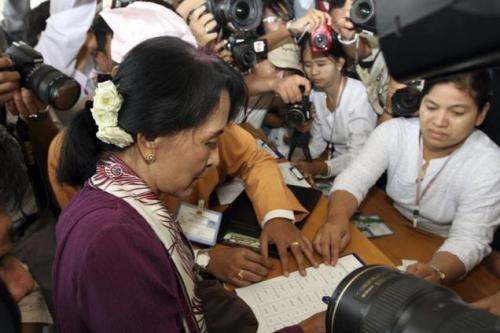Myanmar pro-democracy icon Aung San Suu Kyi registers on attendee's book as she attends a regular session of Myanmar Lower House at Parliament in Naypyitaw, Myanmar on Wednesday