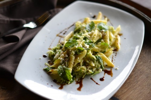 Penne with Zucchini, Ricotta Salata and Mint   Serve 6  Ingredients:  2 lbs small zucchini grated with the large part of a cheese grater 3 tbsp Extra-virgin olive oil Pinch of Salt and Black Pepper 3 tbsp Aged balsamic vinegar 1/2 cup fresh mint leaves, thinly sliced 21 pinches of dried crushed red pepper 2 lbs penne 3 tbsp extra-virgin olive oil 1 cup crumbled ricotta salata  Directions:  1) Sautee zucchini until tender in a bit of olive oil, about 5 minutes.  2) Cook pasta in large pot of boiling salted water until tender but still firm to bite.  3) Drain all but 1 cup. Add pasta and water to zucchini mixture in the sauté pan, then add the rest of the ingredient but the ricotta and cook 3 minutes more.  4) Season to taste with salt and pepper. Finish with ricotta salata