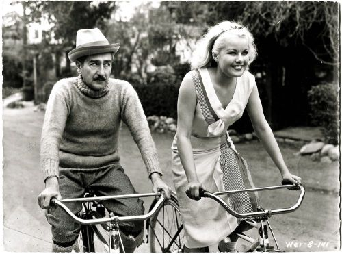 ridesabike:  Adolphe Menjou and Joan Marsh ride bikes.  [look at his eyes…he's plotting something…]