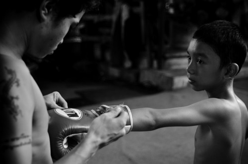 I fight, therefore I survive | Bangkok | Documentary - Young boy boxer looks with admiration at his trainer while he helps him with his gloves.