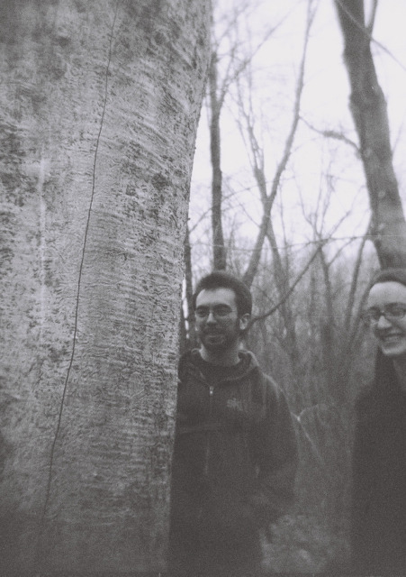 "Holga photo, Dave and Susan checking out Emerald Ash Borer damage on a dead ash tree. Waterloo State Recreation Area in Michigan, early March 2012. The Holga is a ""toy"" cameras, made all out of plastic, even the lens. It's so cheap that it lets in weird light leaks. You can't really focus it or be sure of what exactly is in the frame when you're shooting. That element of surprise, especially because it's a film camera, is what makes it so appealing."