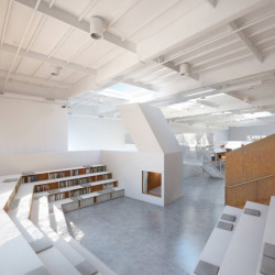 architizer:  An office with an combination amphitheater/library looking over a nap nook