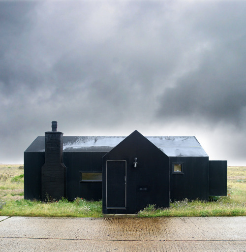 cabinporn:  The Black Rubber House, Dungeness, Kent, UK. Submitted by Paul McNeil.  i love how simple and geometric this house is. i love the navy color, and how it goes well with the grass and flowers and overcast sky. this photo is also really effective— i appreciate that, as well.