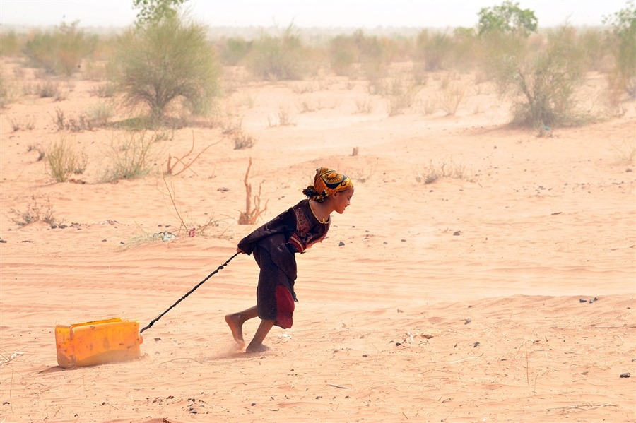 fotojournalismus:  A Malian refugee pulls a jerrican of water at the Mbere refugee camp on May 3, near Bassiknou, southern Mauritania, 60 km from the border with Mali. The fighting in Mali has left more than 60,000 people internally displaced, and a similar number have fled to Mauritania and neighboring countries. Camp Mbere, spread out over a surface area of some 570 km2 receives an average of 1,000 refugees per day, some days even more. According to the LWF representative, in mid-April the camp population was over 55,000, of which more than half were children. [Credit : Abdelhak Senna / AFP / Getty Images]