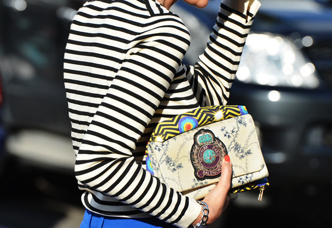 Opt for unexpected parings-bold stripes and a statement clutch.  Image Via: Style.com
