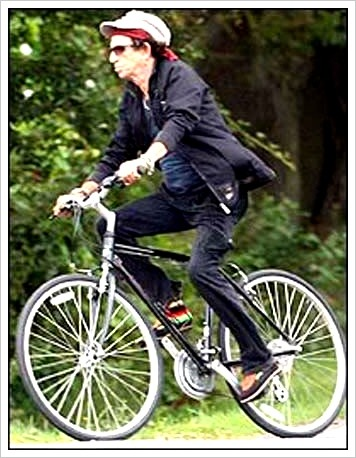 "HAPPY FRIDAY. RIDE YOUR BIKE THIS WEEKEND. Just like Keef. That picture up there of the Stone Rolling reminded me of this, a pricey combo of two of my favorite things: a bicycle and a guitar. Then again, if you're like ""Quaker Songwriter"" Jon Watts, you can forego the fancy, custom I.F. (not to mention just about anything that Mr. Richards would parkake in) and bust freestyle a bit. Egads. E – effin' – gads. Okay, so we're in agreement that we should keep rocking and rolling separate then? Agreed."
