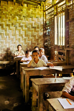 LAOS. Vang Vieng. Boy concentrating in class. ⓒ Julie Mayfeng