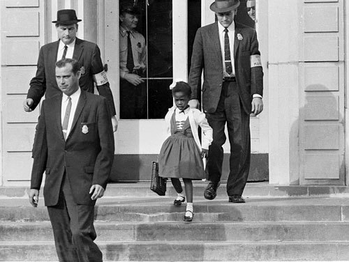 "collective-history:  U.S. Deputy Marshals escort 6-year-old Ruby Bridges from William Frantz Elementary School in New Orleans in November 1960. The first grader was the only black child enrolled in the school.  This photograph was taken over half a century ago. When I think of the story of Ruby Bridges, I sometimes forget that her story doesn't only belong to the history of integration; it belongs to the history of New Orleans. Growing up so far from New Orleans, I was prone to contextualizing her story with that of the Little Rock Nine, Rosa Parks, Martin Luther King, Jr., and the rest of the Civil Rights Movement. Taking a class on New Orleans helped me focus on the city itself. William Frantz Elementary School is located in the Upper 9th Ward on North Galvez Street, very much a part of New Orleans. The Times Picayune called her an ""icon of New Orleans integration"" — not just United States integration. She was the first black person to attend public school in New Orleans. Her brother was shot and killed on the streets of New Orleans in 1993, so she went back to her old elementary school again to bring her nieces and nephews the terrible news. In 2009, she sat on the school steps, with William Frantz Elementary boarded  up behind her in the wake of Hurricane Katrina. She wanted to reopen the school under her name with a focus on social justice. Although the school reopened in 2010, the mayor decided not to rename the school after her.  Rose, Chris. ""Ruby Bridges, an Icon of New Orleans Integration, Will Witness Another Milestone 50 Years Later."" NOLA.com. The Times Picayune, 18 Jan. 2009. Web. 15 May 2012. <http://blog.nola.com/news_impact/print.html?entry=/2009/01/olibbp104plv2lvcrtop1_0119aaa0.html>. Chang, Cindy. ""Landrieu News Release Was Wrong: Mayor Did Not Rename William Frantz Elementary."" NOLA.com. The Times-Picayune, 20 May 2010. Web. 15 May 2012. <http://blog.nola.com/education_impact/print.html?entry=/2010/05/landrieu_press_release_was_wro.html>"