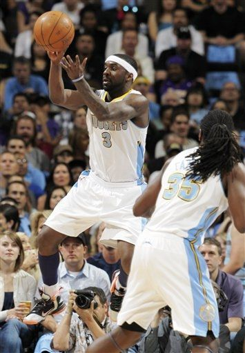 Denver Nuggets guard Ty Lawson, back, takes to the air to pull in the ball as forward Kenneth Faried looks on against the Los Angeles Lakers.