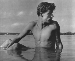 Boy seated in the water, by Herbert List (1950).