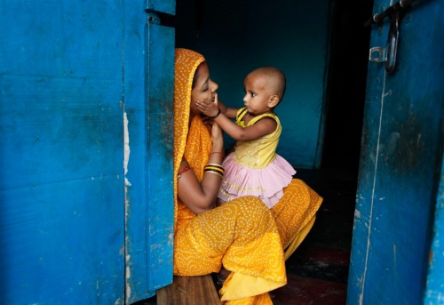 An Indian woman plays with her child at the doorway of her house ahead of Mother's Day, in Allahabad, India, May 6. Mother's Day will be celebrated on May 13.