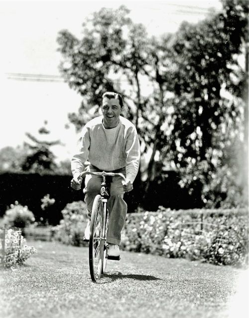 "Lyle Talbot rides a bike. Snipe: ""Lyle Talbot a-wheel through a Beverly Hills lane. The young player is seen with Marion Davies in ""Page Miss Glory,"" a cosmopolitan comedy for Warner release."""