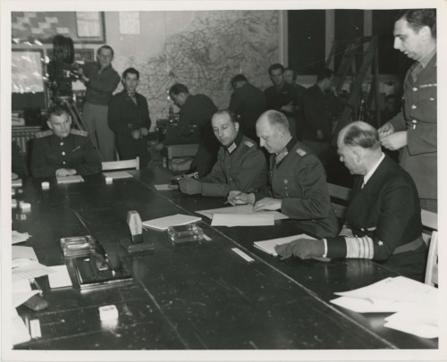 ourpresidents:  The Unconditional Surrender of Germany On May 7, 1945, the European conflict of World War II ended when Germany signed an unconditional surrender at Allied headquarters in Rheims, France. In this photo, Colonel General Gustaf Jodl, German Chief of Staff signs the documents of unconditional surrender, under which all remaining forces of German Army are bound to lay down their arms.   On Jodl's left is General Admiral Von Friedeburg of the German Navy, on his right is Major Wilhelm Oxenius of the German General Staff.   -from the FDR Library