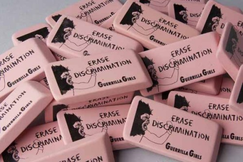 Image: A pile of pink erasers reading 'Erase Discrimination: Guerrilla Girls' with a woman wearing a gorilla mask.